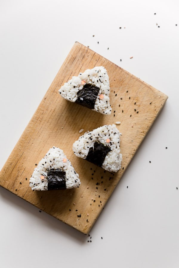 Top down image of three onigiri rice balls on a wooden chopping board.