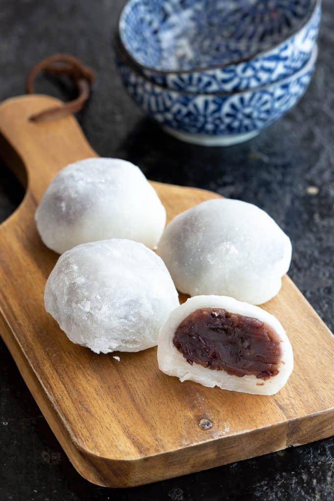 Four mochi on a wooden board.