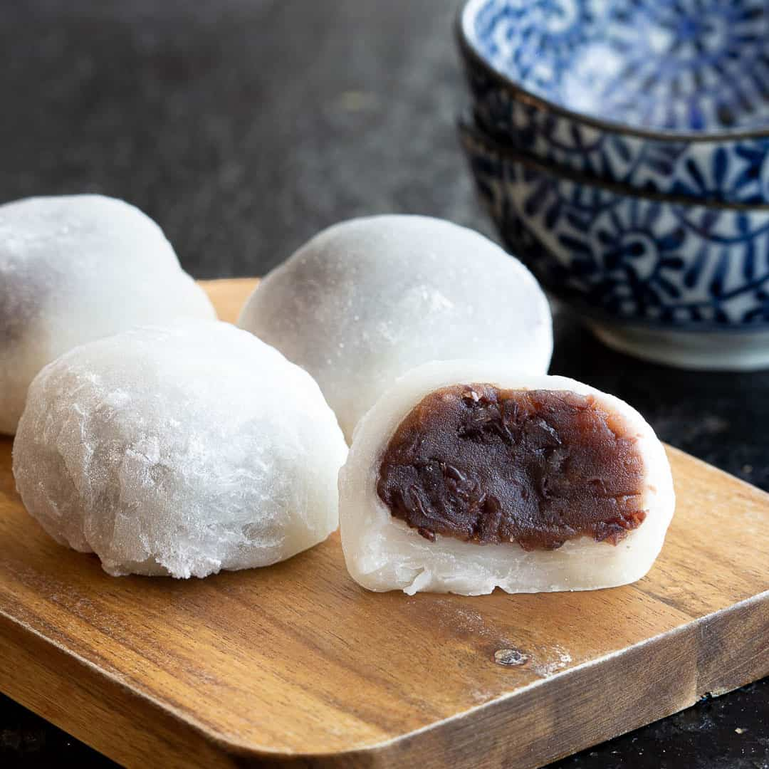 Mochi on a board with an open one showing red bean paste.