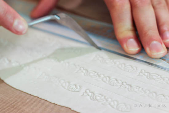 Cutting sugarcraft lace ribbon for the hat.