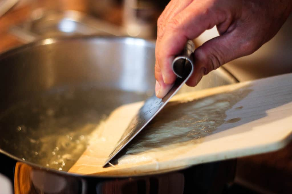 Bavarian Spatzle Recipe - Chopping the pasta dough into the boiling water takes skill, the water from the steam can be really hot!