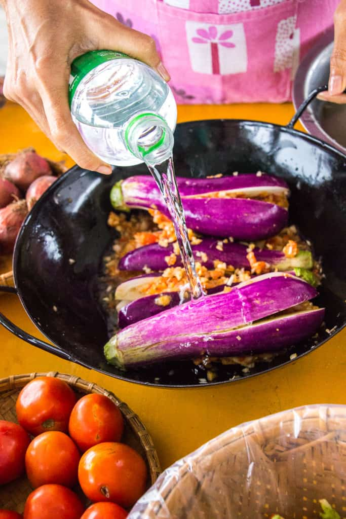 Pouring water into the wok with the stuffed eggplants.