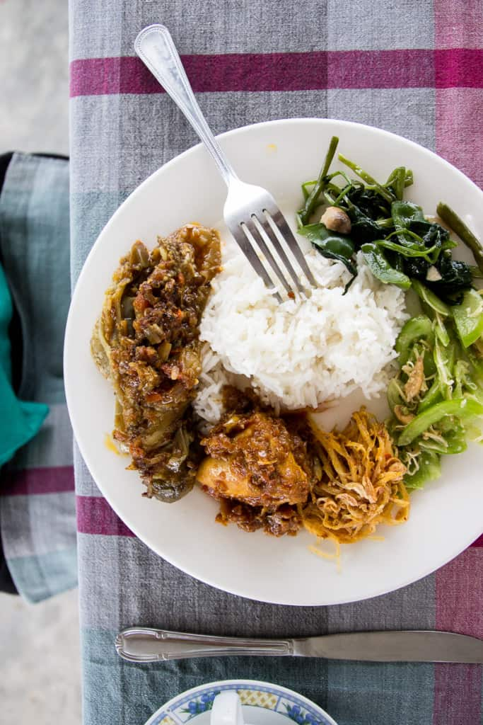 A plate of small portions of burmese foods like eggplant curry and lemongrass chicken with steamed rice in the middle.