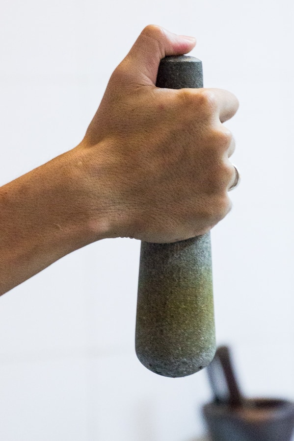 Hand gripping a mortar and pestle, with thumb pressing on top for stability.