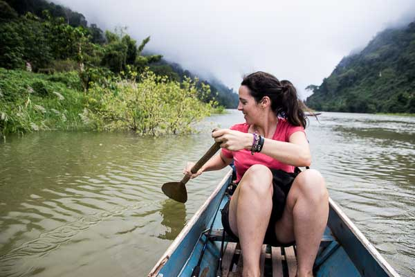 10 Months Eating on the Road - Sarah guiding the little fishing boat along nicely in Nong Khiaw, Laos.