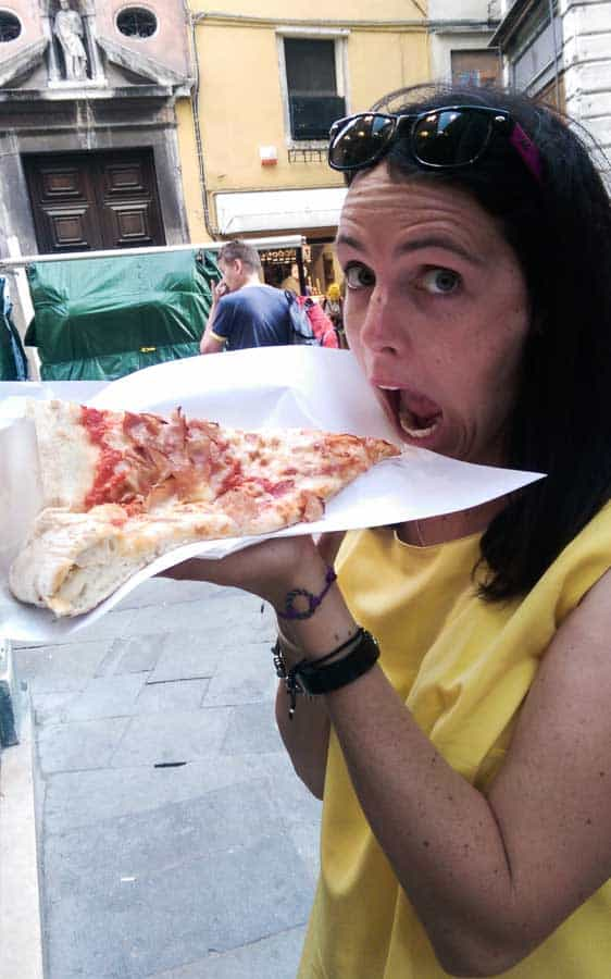 10 Months Eating on the Road - Sarah eating a delicious, delicious slice of cheesy pizza goodness in Venice.