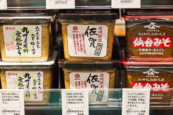 Yellow (shinshu) miso paste containers on a supermarket shelf.