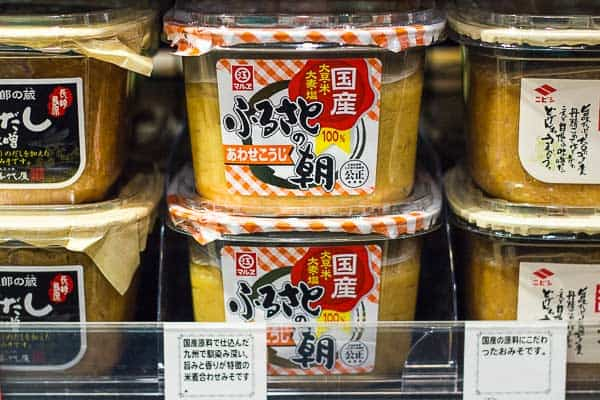 Containers of miso on a supermarket shelf.