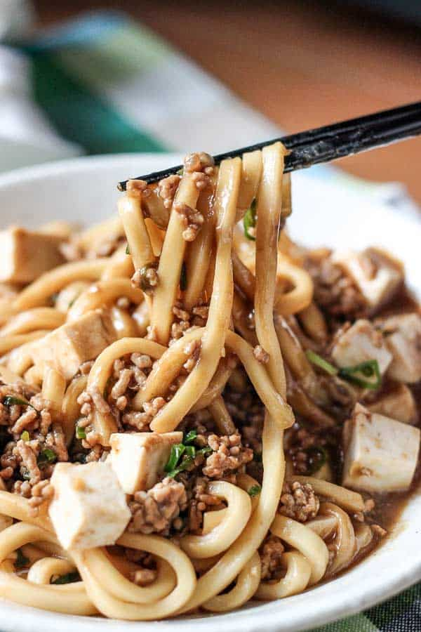 Bowl of Mapo Tofu udon noodles held up with chopsticks.