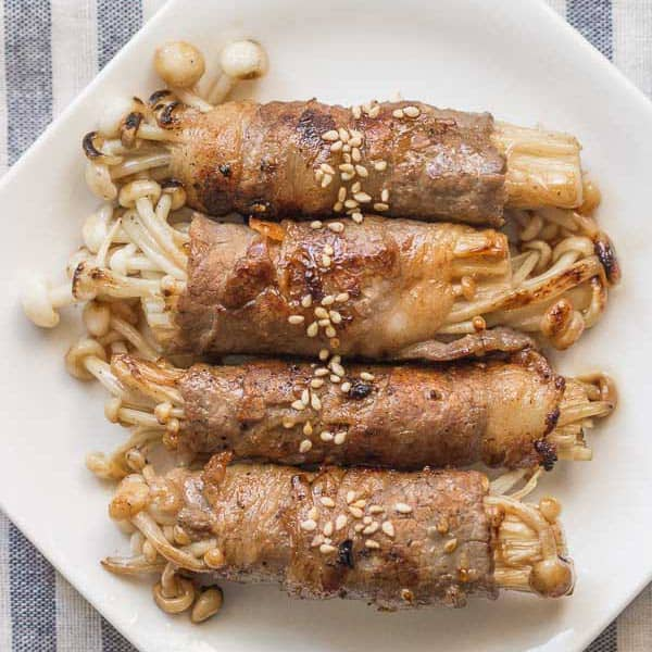 Enoki beef rolls on a white plate.