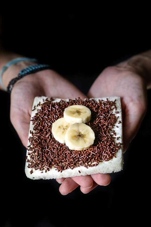 A slice of white bread topped with banana and chocolate sprinkles.