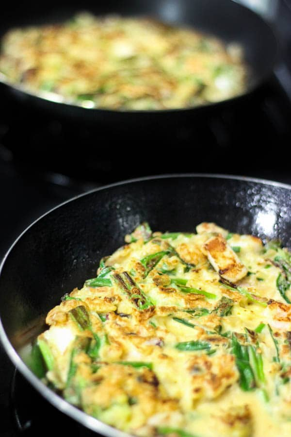 Crispy Korean Kimchi Seafood Pancakes - Known as Haemul Pajeon, this is commonly found on the streets of South Korea. A quick, crispy and crunchy snack just waiting to be flipped onto your plate at home.   wandercooks.com