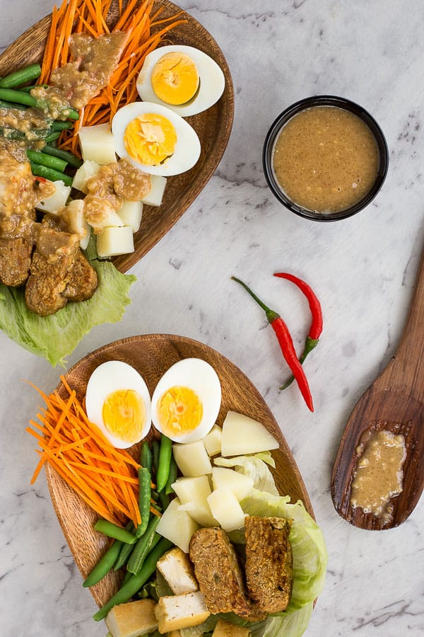 Two platters of Indonesian gado gado salad with a small bowl of dipping sauce.