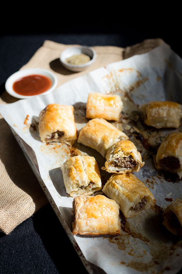 A tray of sausage rolls with dipping sauces.