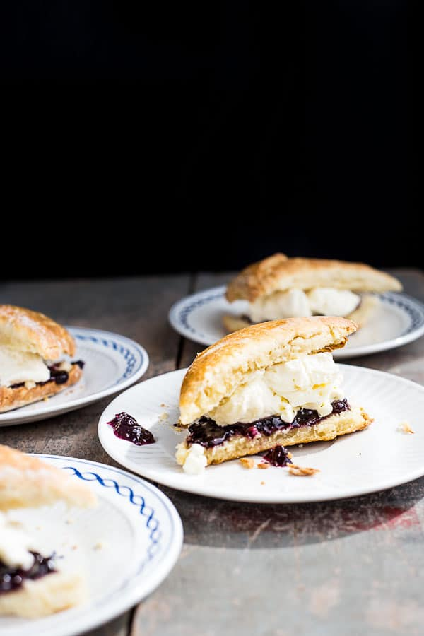 Four plates of scones sliced and served with cream and jam.