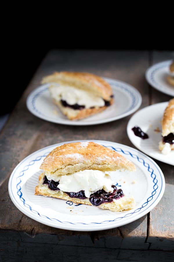 Several plates of scones with jam and cream.