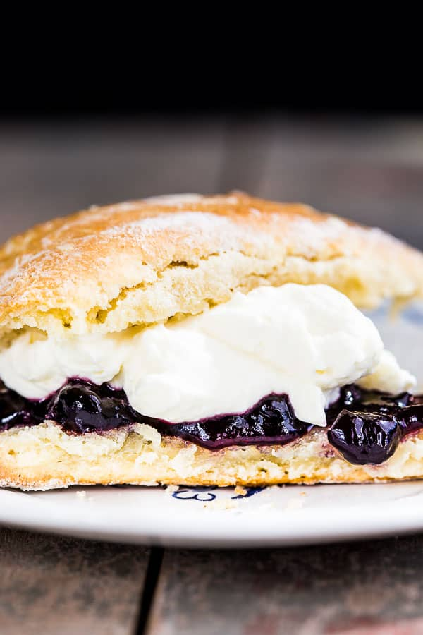 Close up shot of a single scone sliced in half, filled with cream and jam.