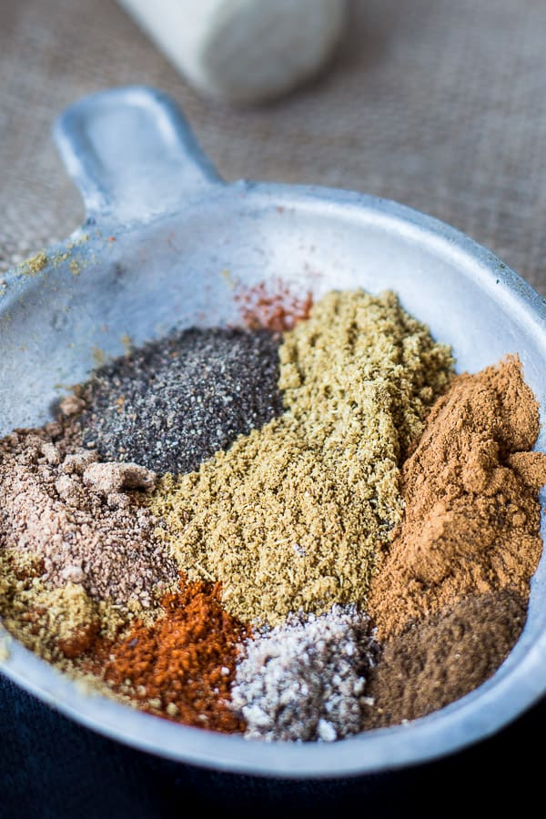 All the spices needed for baharat in a silver serving dish.