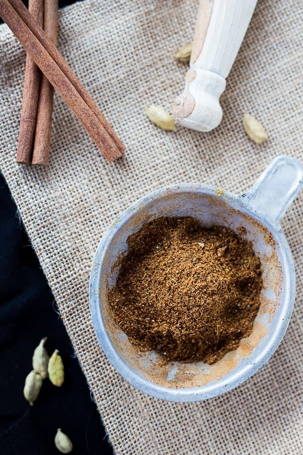 Blended baharat spices in a dish, on a mat with whole cinnamom sticks and cardamon pods.