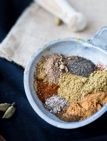 Baharat spices in a dish next to cardamom pods.