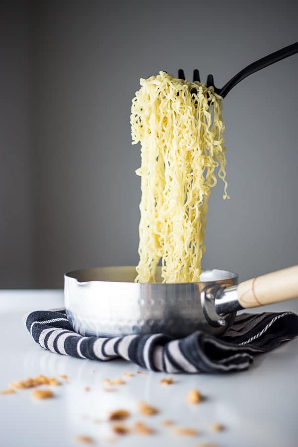 Cooked instant noodles being scooped out of a saucepan.