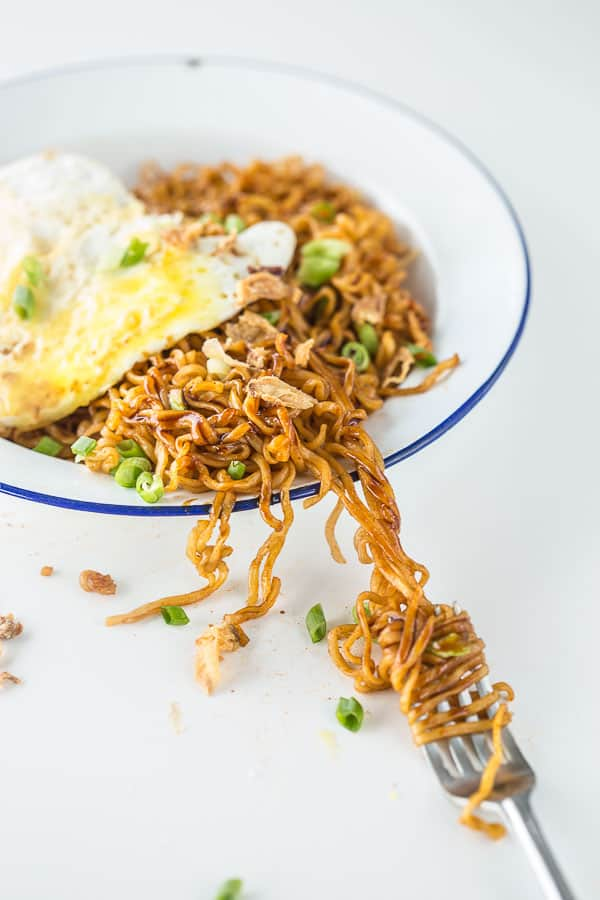 Fried noodles on a plate being twirled with a fork.