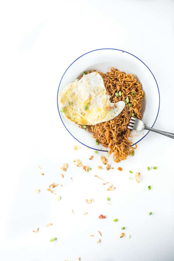 Stir fried noodles on a plate with fried egg and shallots.