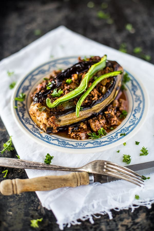 Karniyarik eggplant on a plate garnished with slices of green bell pepper, a knife and fork in the foreground.