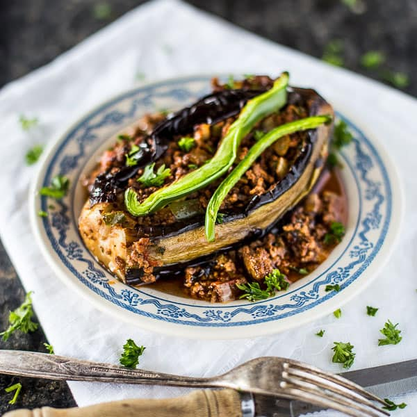 Stuffed eggplant on a plate garnished with slices of green bell pepper.