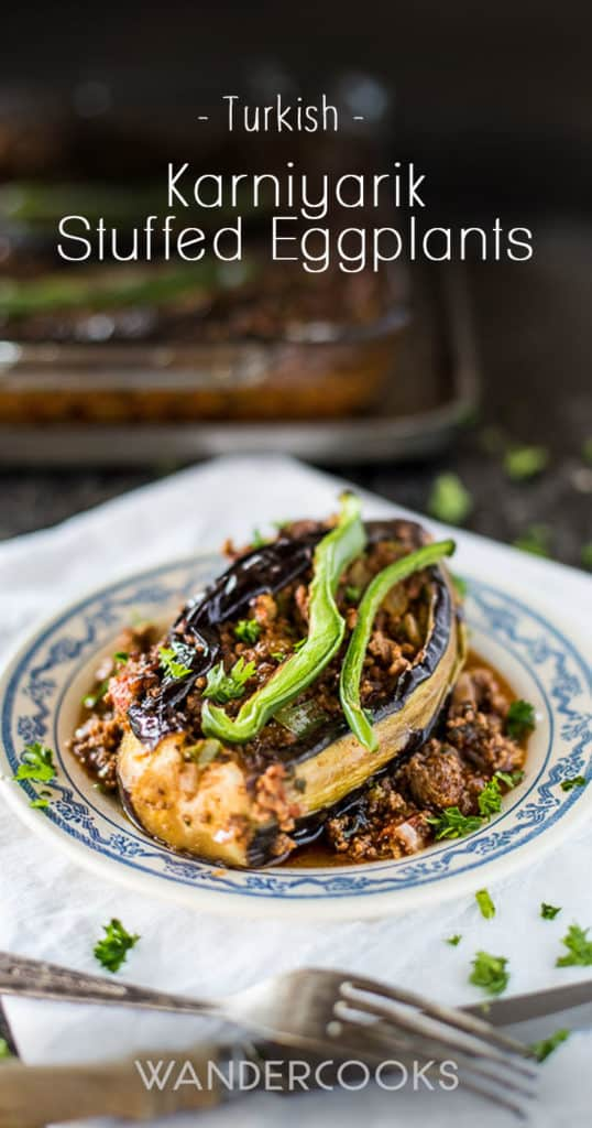 Karniyarik stuffed eggplant on a plate with the tray of cooked eggplants in the background.