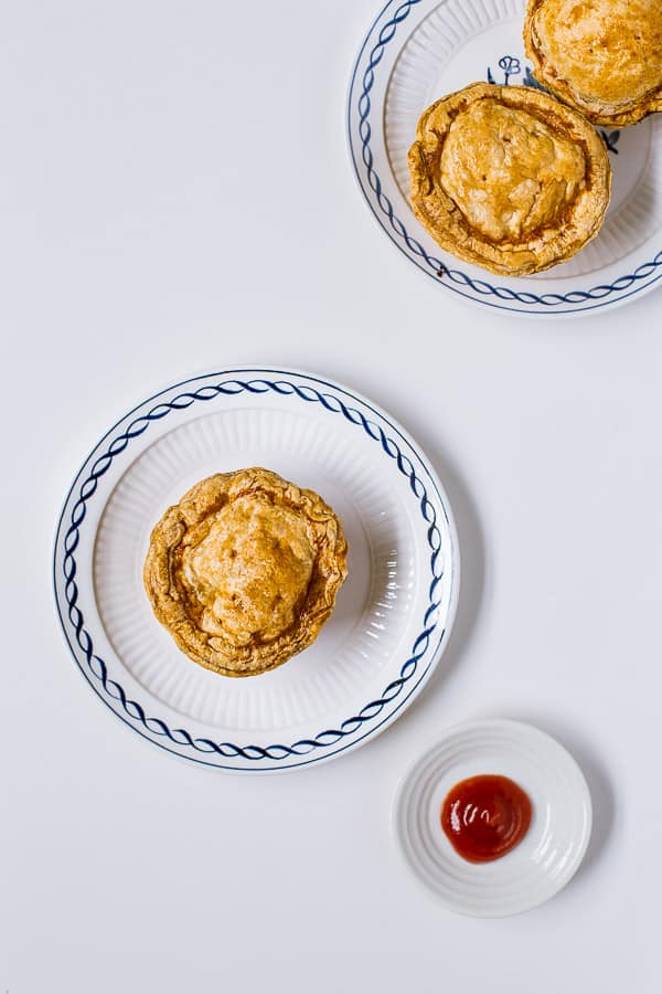 Party pies on plates next to tomato sauce.
