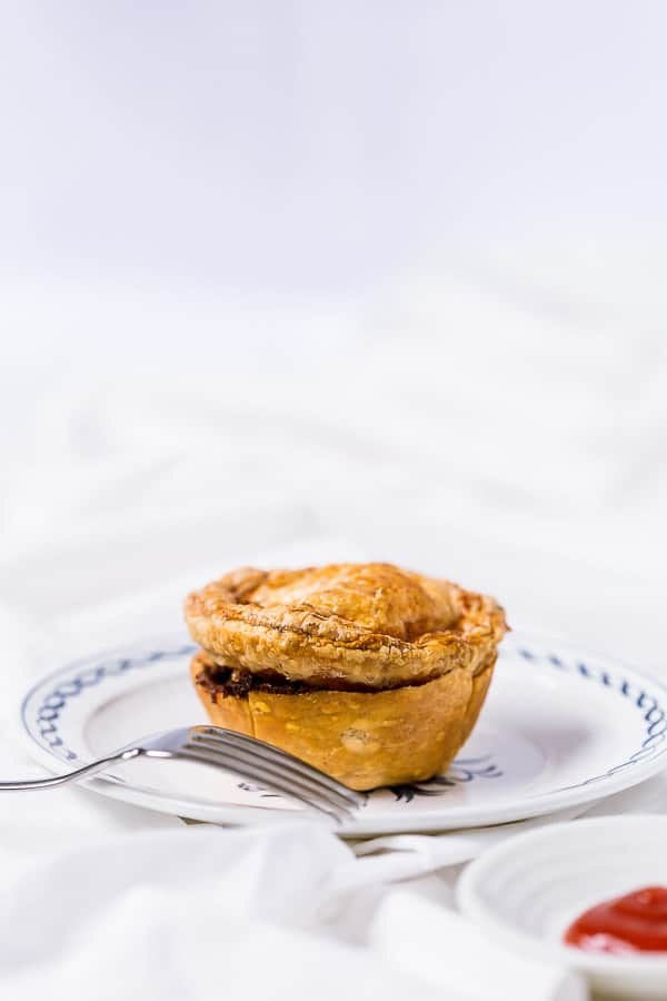 A party pie on a plate next to a fork.