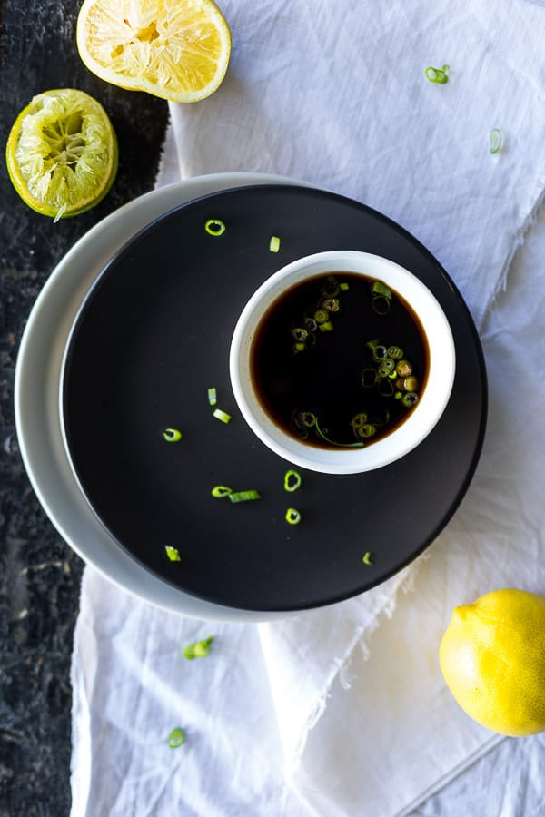Ponzu sauce in a dipping bowl garnished with spring onion, next to squeezed lemon and lime.