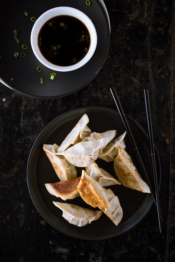 A plate of cooked pork dumplings next to a bowl of dipping sauce.
