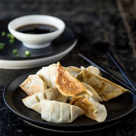 Fried pork gyoza dumplings on a plate with dipping sauce in the background.