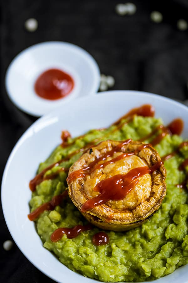 A mini meat pie floating on mushy pea soup, slathered in tomato sauce.