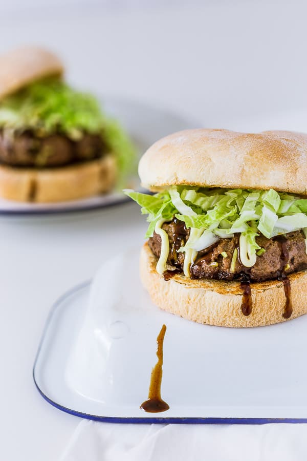 Two Japanese hamburgers with fresh cabbage, slathered in bbq sauce and mayo.