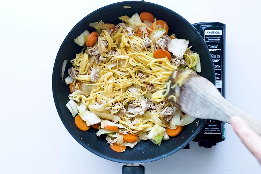 Yakisoba noodles in a pan being stirred.