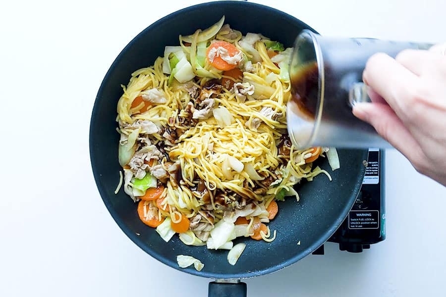 Frying pan with Yakisoba noodles and sauce being added.