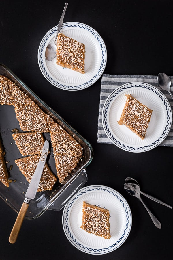 Top down view of a tray of cooked semolina cake, with slices portioned out onto three plates.