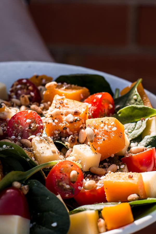 Close up shot of pumpkin, cherry tomatoes, cheese and leafy greens in a bowl sprinkled with crunchy dukkah.