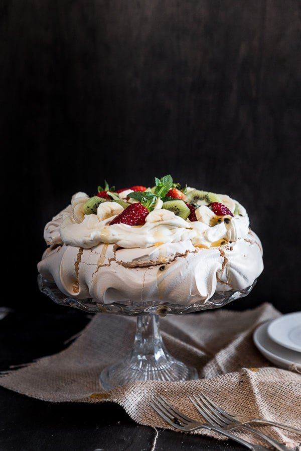 Pavlova on a cake stand covered with sweet whipped cream and fresh fruit.