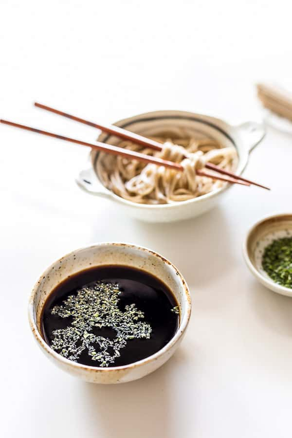 A bowl of mentsuyu noodle sauce next to cooked soba noodles.