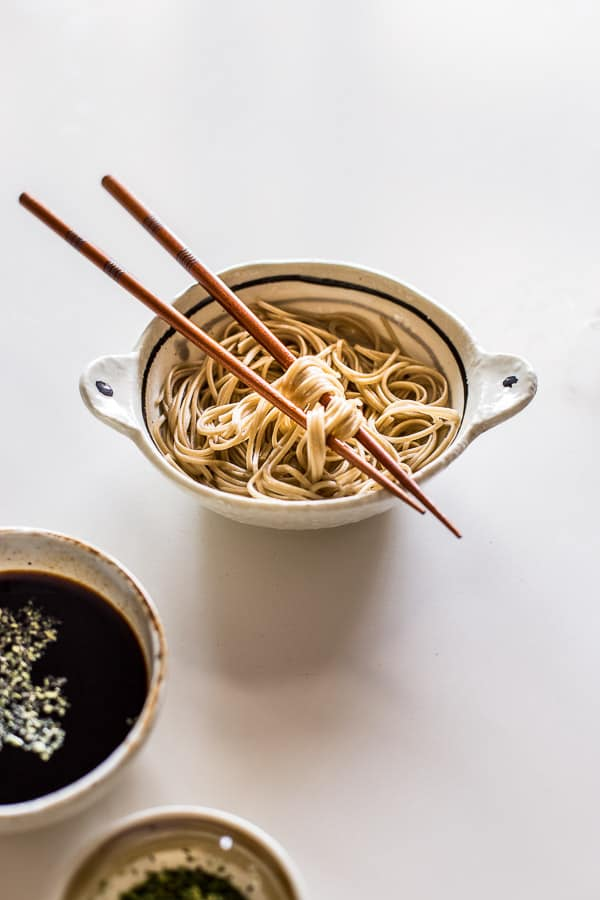 Noodles wrapped around a pair of chopsticks resting on a small bowl.