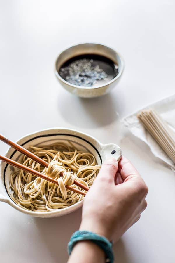 A hand placing a bowl of noodles on the table next to a small bowl of noodle sauce.