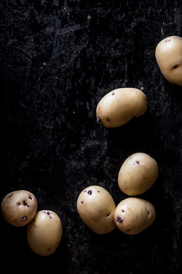 Top down view of white potatoes on a black background.