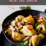 Bowl of potatoes with curry leaves and chilli.