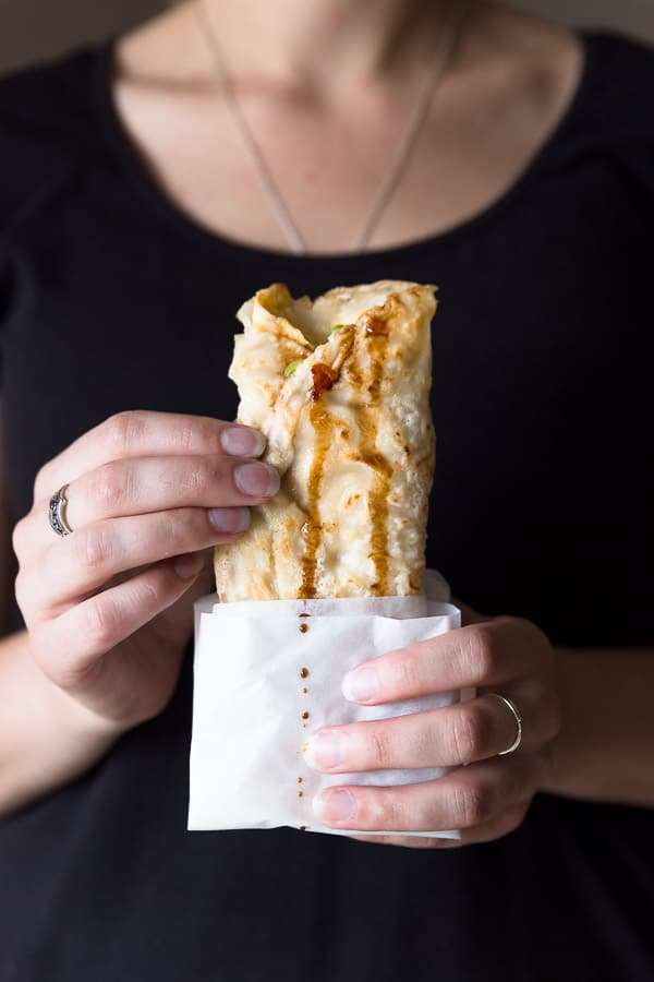 A person holding a freshly cooked dan bing crepe, ready to eat.