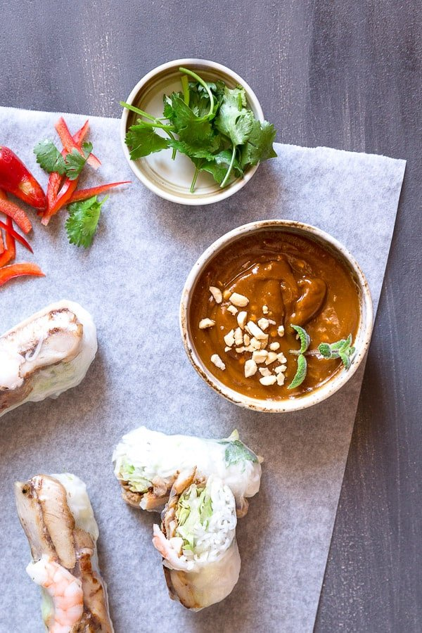 Top down view of peanut hoisin sauce beside a sliced summer roll and fresh herbs.