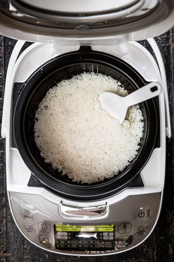 Cooked rice in a rice cooker with a rice paddle.